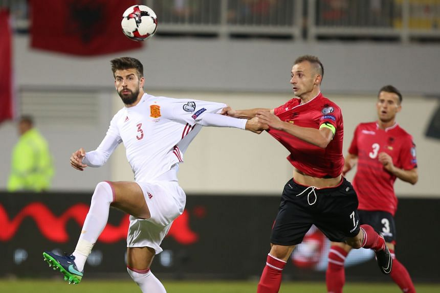 Albania's Ansi Agolli and Spain's Gerard Pique give each other some close attention during the World Cup qualifier in Shkoder on Sunday. Spain won 2-0 but Pique was criticised for cutting the national colours off his sleeves.