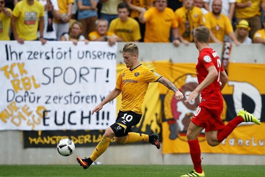 """Dynamo Dresden's Marvin Stefaniak (in yellow) in German Cup action with RB Leipzig's Benno Schmitz. The banner that was displayed by Dynamo fans reads: """"You destroy our sport! For this we will destroy you!!!"""""""