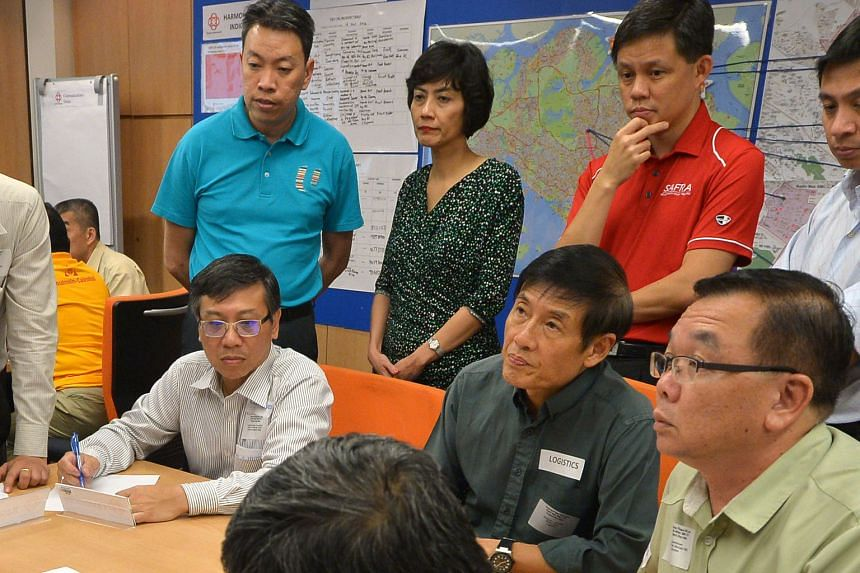 (From left) Tanjong Pagar GRC MPs Melvin Yong (in blue), Joan Pereira and Chan Chun Sing, who is Minister in the Prime Minister's Office, observing the exercise at Buona Vista Community Club.