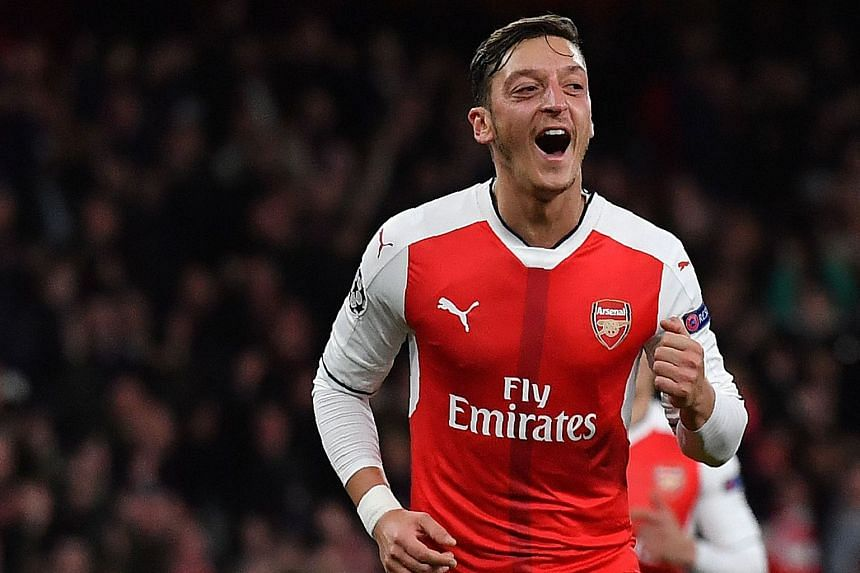 Midfielder Mesut Ozil celebrates scoring Arsenal's sixth goal during their Champions League Group A clash against Ludogorets Razgrad at The Emirates Stadium. His close-range volley in the 87th minute completed his hat-trick - the first treble of his