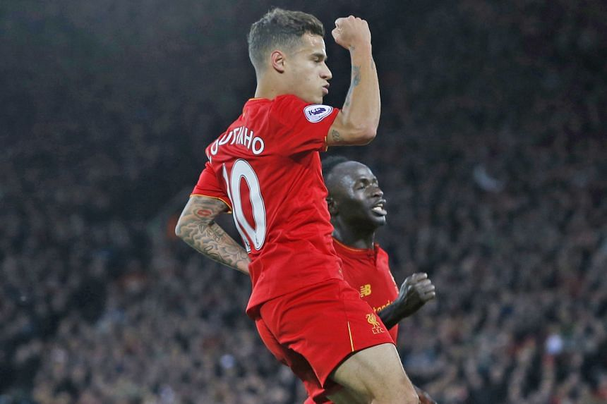 Brazilian Philippe Coutinho celebrating scoring Liverpool's second goal with Senegalese Sadio Mane, who had opened accounts. Gareth McAuley reduced arrears but the Reds hung on for full points, to go second behind Arsenal on goal difference ahead of