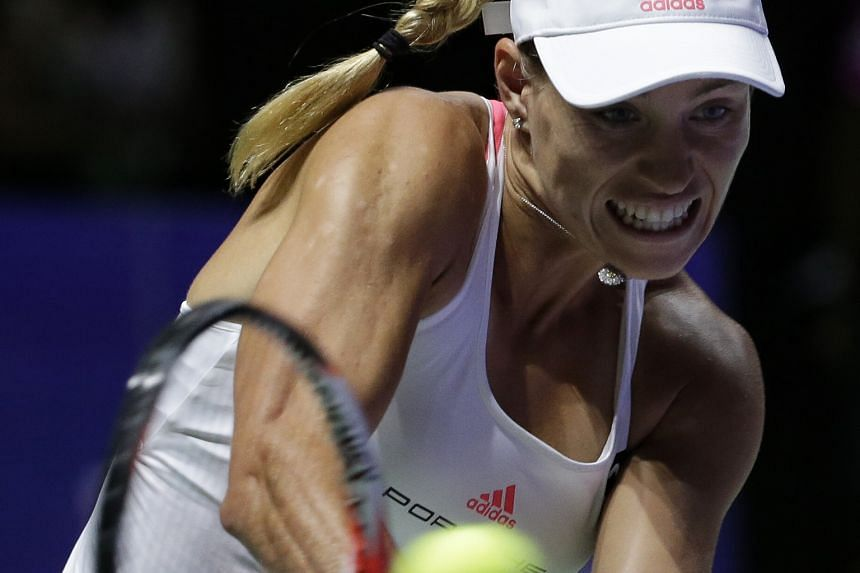 Angelique Kerber of Germany hitting a backhand against Slovakia's Dominika Cibulkova during their WTA Finals opener yesterday. Top-ranked Kerber proved her fighting qualities by coming from behind in the third set to seal a 7-6 (7-5), 2-6, 6-3 victor