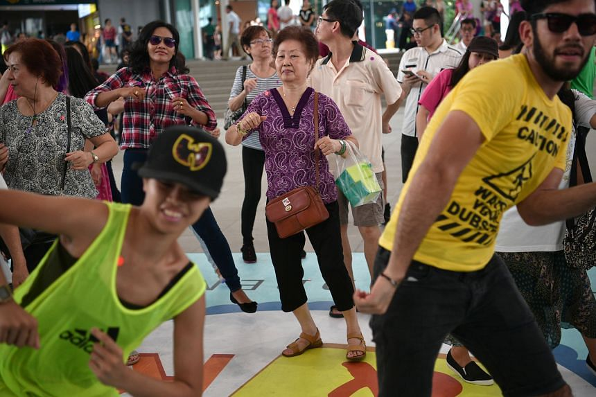 Madam Tan (centre, who declined to give her full name but said she is in her 70s) dancing with a plastic bag containing cakes at Bedok Town Square on Sunday. She was among almost 1,000 members of the public who took part in Unlock And Roll, an event