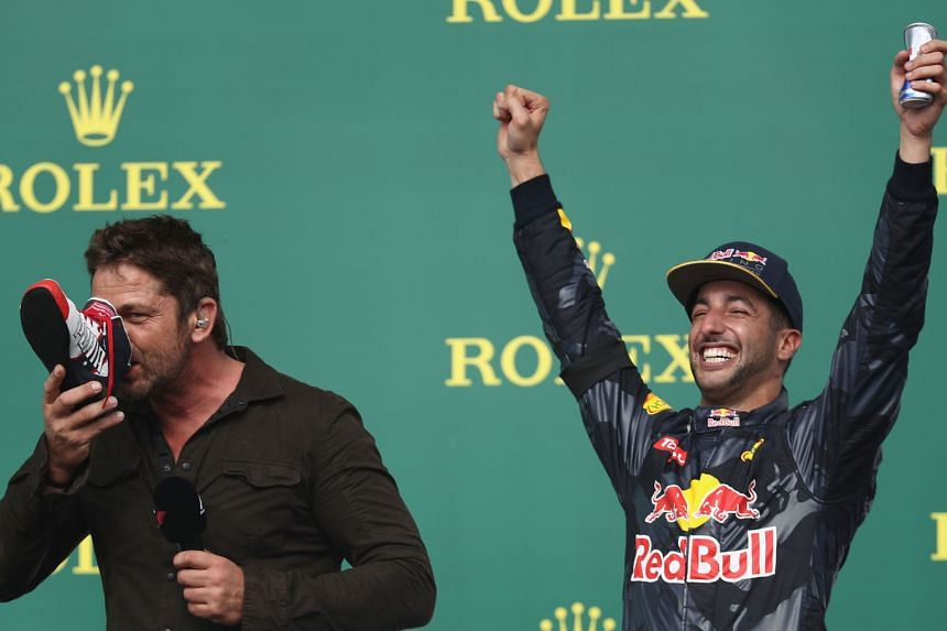 """Scottish actor Gerard Butler, egged on by Australian Red Bull driver Daniel Ricciardo, who finished third in the US Grand Prix, sportingly does a """"shoey"""" on the podium after the race in Austin, Texas on Sunday."""