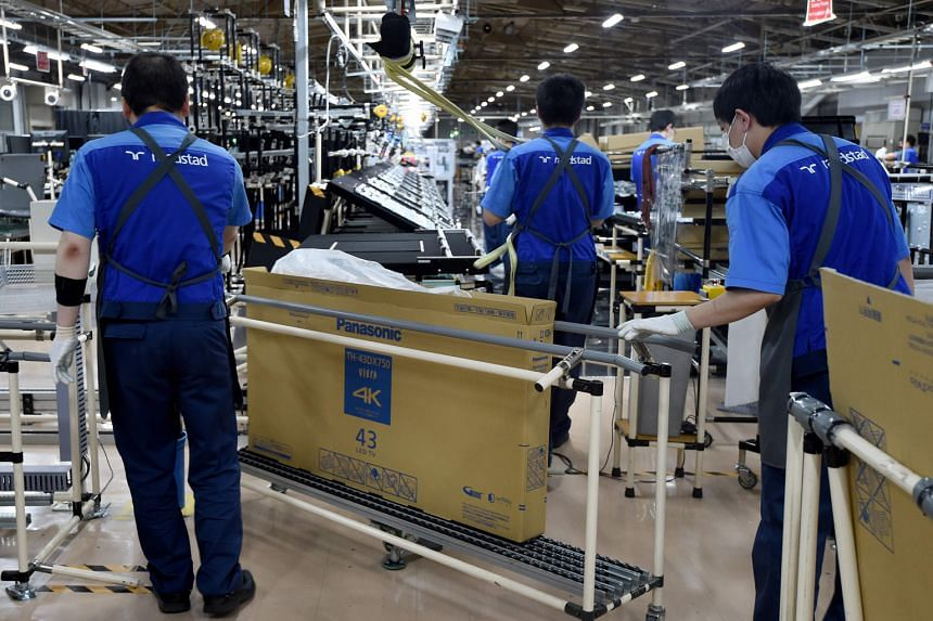 Workers at a plant in Utsunomiya, some 100km north of Tokyo, which assembles TV sets for Panasonic. Japan's exports fell 6.9 per cent last month from a year earlier, following a 9.6 per cent decline in August.