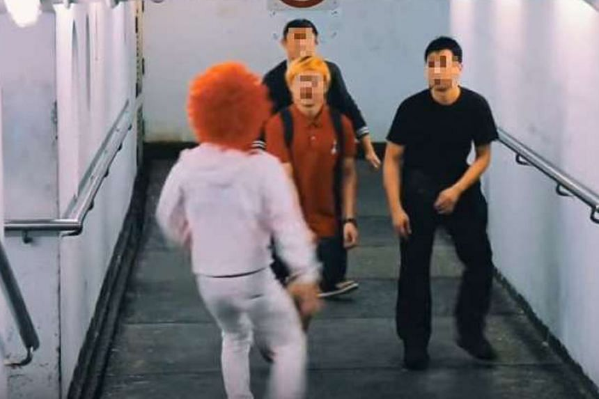 A screenshot from the video showing a man in a clown outfit trying to scare passers-by.