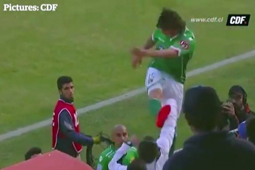A screen capture of Argentinian forward Sebastian Pol, from Chilean top-flight side Audax Italiano, kicking the fan, Cristobal Aztorquiza, after climbing the fence around the pitch.