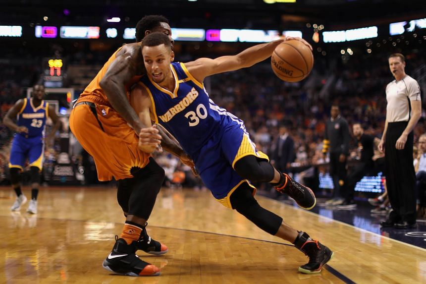 Golden State guard Stephen Curry trying to slash past Eric Bledsoe of the Phoenix Suns en route to the basket in a 106-100 victory on Sunday.