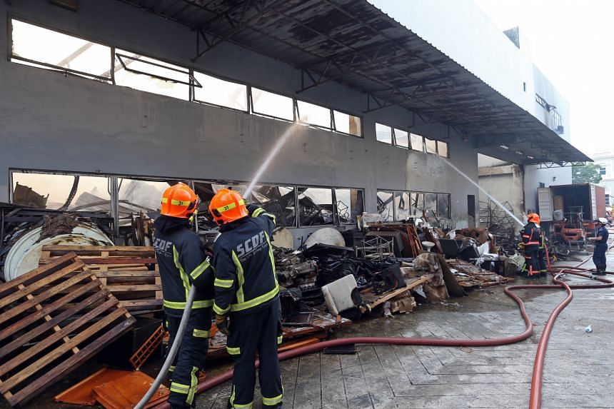 Firefighters putting out the blaze at the three-storey warehouse leased by furniture dealer Winter International Group at 65 Sungei Kadut Loop yesterday morning. The SCDF said it was alerted to the fire at about 5am and found three people trapped on