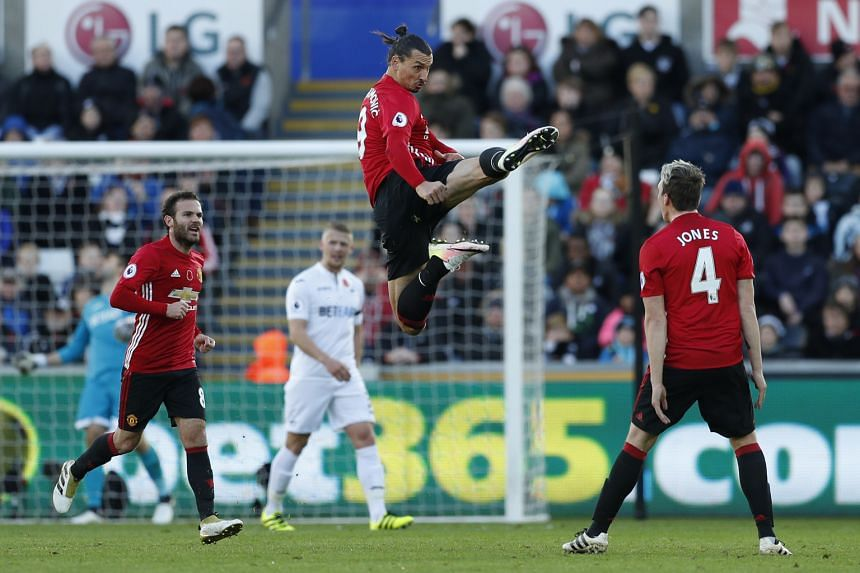 Zlatan Ibrahimovic letting fly with a karate kick a la ex-Manchester United legend Eric Cantona, as he celebrates scoring United's second goal - the striker's first in seven games - against Swansea with team-mate Phil Jones. Record signing Paul Pogba
