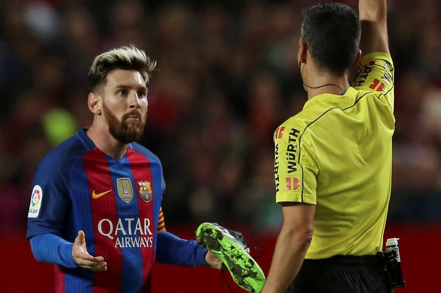 Lionel Messi being booked for time wasting as Barcelona held out for a 2-1 Spanish Primera Liga victory at Sevilla. The Argentinian needed his boots replaced after being tackled, but took his time getting off the ground and was cautioned while headin