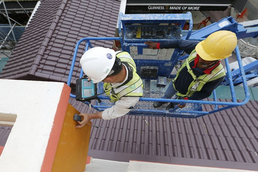 A tester using ultrasound scanning equipment to inspect a sunshade at the Tampines block where another sunshade was partially dislodged in September. Mr Wong said his ministry will review its policies and benchmark them against those of other high-ri