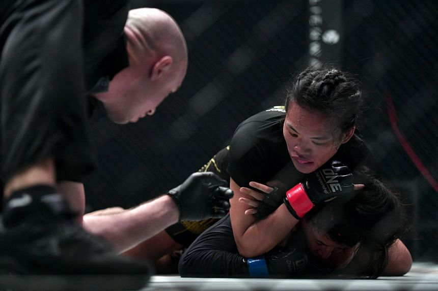 Tiffany Teo (top) grappling with Egyptian Walaa Abbas during their One Championship: Defending Honour flyweight bout at the Singapore Indoor Stadium last night. The Singaporean won after Abbas tapped out to a rear-naked choke at 4min 15sec in the sec