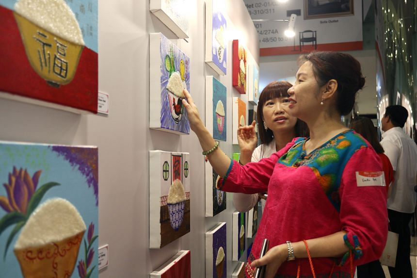 Ms Belinda Chua (in white), 53, wife of artist Tan Kay Nguan, showing a guest a painting for sale at Marina Square Linkbridge Atrium yesterday. More than a hundred rice bowls, painted on canvas with acrylic, adorned the space, as part of a charity dr