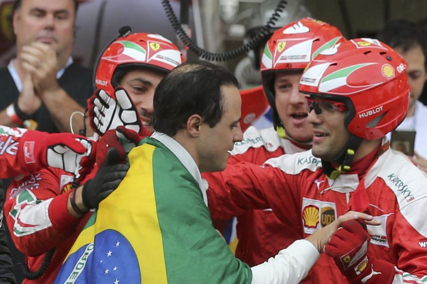 Draped in the Brazilian flag, Williams' Felipe Massa is greeted by members of his former team Ferrari in the paddock.