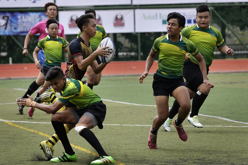 Pioneer Secondary players having a hard time trying to stop Anglo-Chinese School (Barker Road) winger Danish Rusydi Sidek in their U-16 group game during the Saints 7s rugby tournament at St Andrew's Junior College on Saturday.