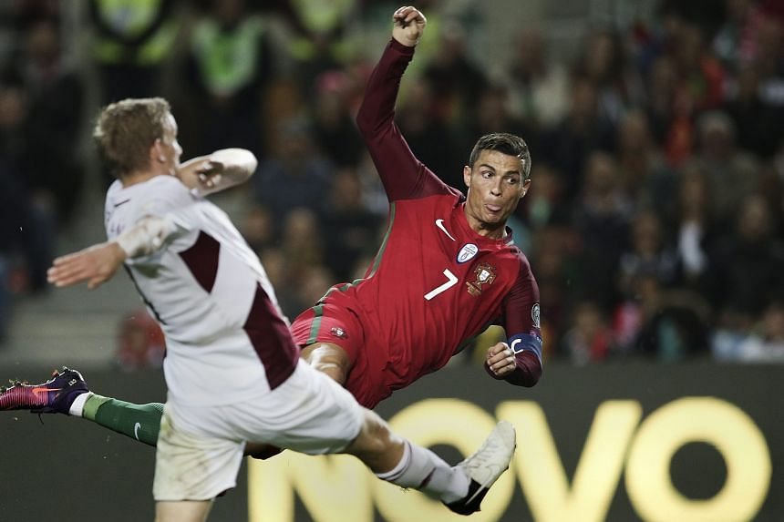 Cristiano Ronaldo (right) scoring Portugal's third goal in the 4-1 win against Latvia in the World Cup qualifying match at Algarve Stadium, Portugal, on Sunday.