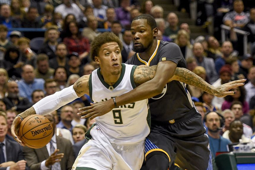 Milwaukee Bucks' Michael Beasley driving to the basket against Kevin Durant of the Golden State Warriors, who won the NBA game 124-122.
