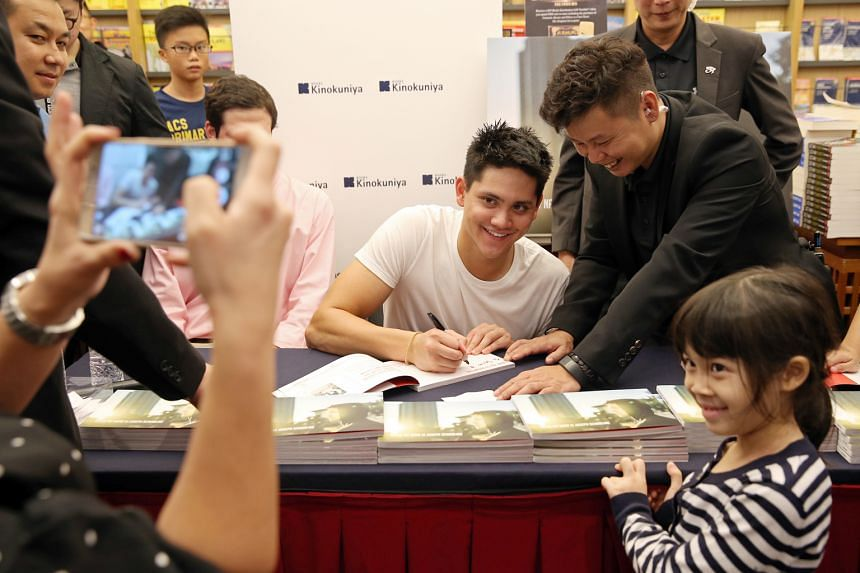 Joseph Schooling signing an autograph for Jenna Wong, seven, at a session for his photo book titled Hello, My Name Is Joseph Schooling at Kinokuniya, Ngee Ann City.