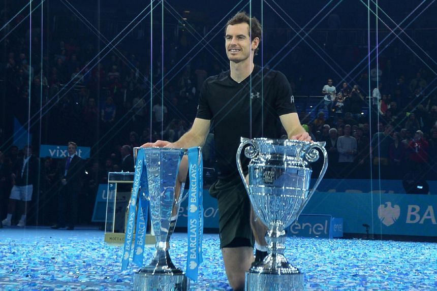 Andy Murray posing with the ATP World Tour Finals trophy (left) as well as the world No. 1 trophy after defeating Novak Djokovic 6-3, 6-4 at London's O2 Arena on Sunday to finish the year as the top male player.