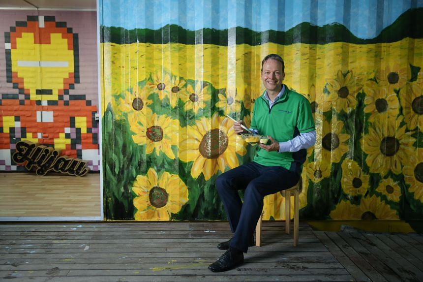 Mr Buchner, seated in front of the painted container walls at Ground-Up Initiative, a non-profit community-driven community in Yishun that believes in sustainable living and that has partnered AkzoNobel. Under Mr Buchner's charge, AkzoNobel went one
