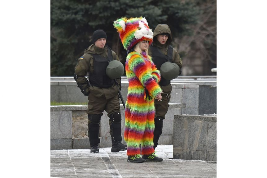 Ukrainian National Guard members walking past a woman wearing a colourful costume as they patrolled near Independence Square in Kiev yesterday, following a night of violence by activists of some far-right Ukrainian parties. Kiev police said they were