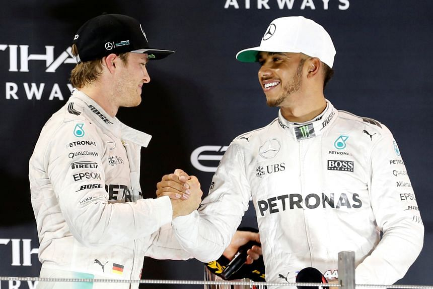 """Nico Rosberg (left) shakes hands with team-mate Lewis Hamilton after a tense finish to the race. The Briton was repeatedly ordered to speed up by Mercedes but replied: """"Let us race."""""""