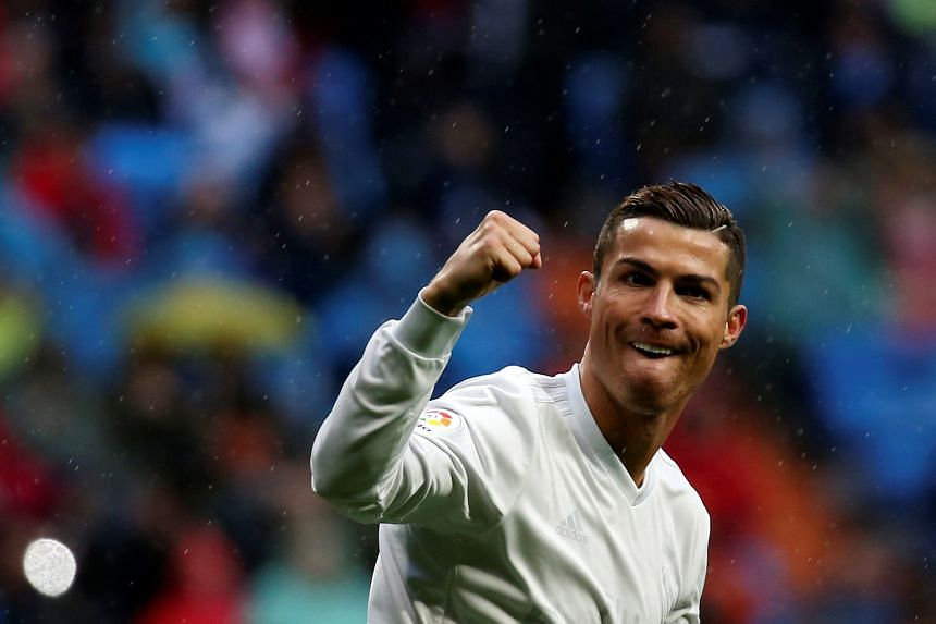 Cristiano Ronaldo celebrating one of his two goals against Sporting Gijon to help cement Real Madrid's position atop Spain's La Liga.