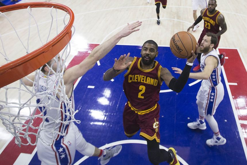 "Cleveland Cavaliers' Kyrie Irving evading the attention of Philadelphia 76ers guard Nik Stauskas in making a play for a basket. The Cavs point guard's ""hot hand"" in the fourth quarter meant he took on his team's scoring responsibility in the game's l"
