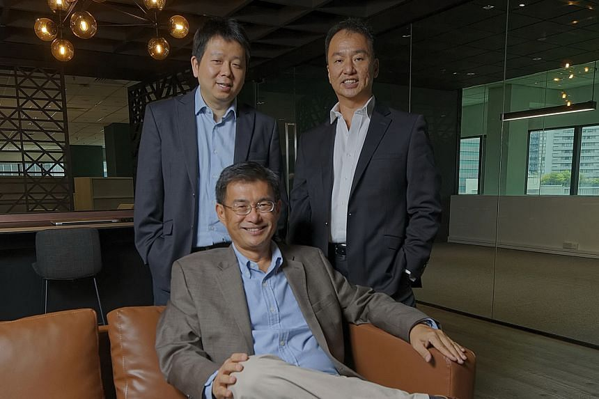 Spark Systems co-founder and chief executive Wong Joo Seng (seated) with chief technology officer Ye Ting Song (left) and chief operations officer Jason Wang Kee Huat. Spark Systems aims to eventually develop a Singapore-based foreign exchange market
