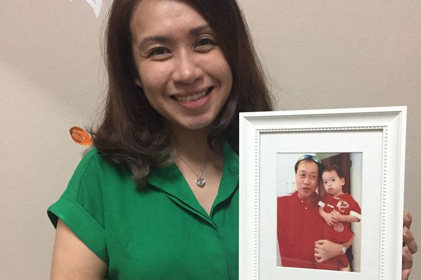 Ms Tan with a photo of her son and late father. The diamond she has on is made from her dad's ashes.