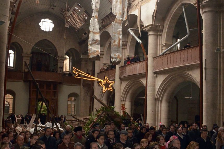 Worshippers attending mass on Christmas Day at the war-ravaged St Elias Cathedral in Aleppo's Old City.