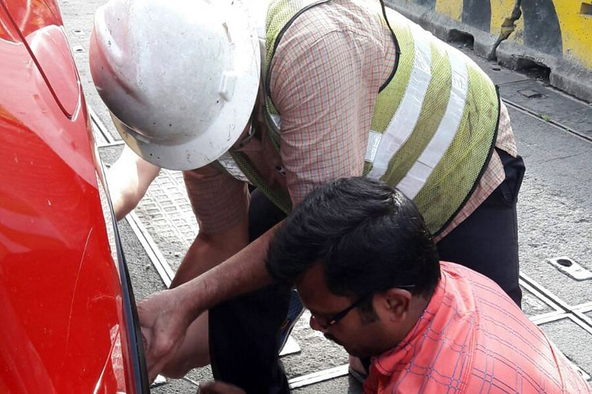 Mr Venkateswaran (in red), a lorry driver from India, was one of two people who helped to replace a motorist's car tyre on Wednesday.