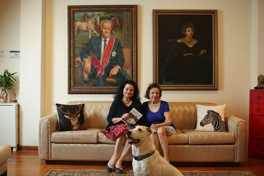 Mrs Gloria Barker and her daughter Carla with the newly released book on the late E.W. Barker, Singapore's pioneering law minister, whose portrait hangs behind them. Mr Barker was best known for drafting and finalising, in just 10 days, the separat