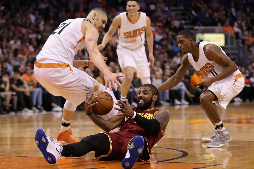 Cleveland's Kyrie Irving beating (from left) Phoenix's Alex Len, Devin Booker and Brandon Knight to recover a turnover in their NBA game. The Cavs enjoyed big leads at the end of each of the first three quarters but had to fend off the Suns' late com