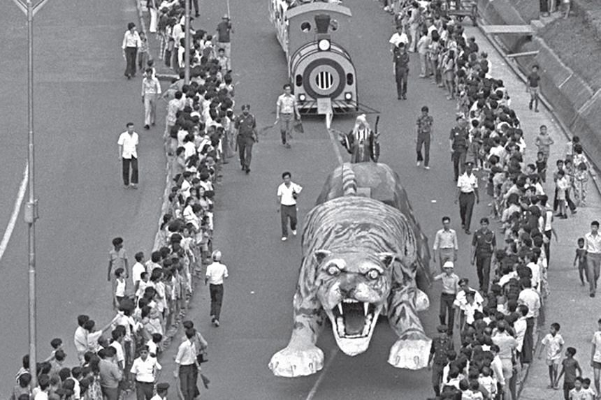 Left: PA's Dr Ang (in red) and Mr Seow Choke Meng (fourth from left), business consultant of the Chinese Media Group and Times Properties of SPH, with Chingay performers at the book launch. Above: The Chingay Parade in 1974 featured a 9m-long tiger f
