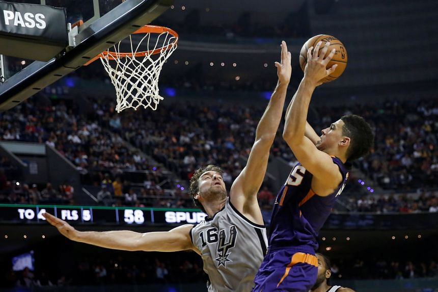 Suns guard Devin Booker challenges Spurs centre Pau Gasol at the rim during an NBA game in Mexico City. Booker finished with a game-high 39 points.