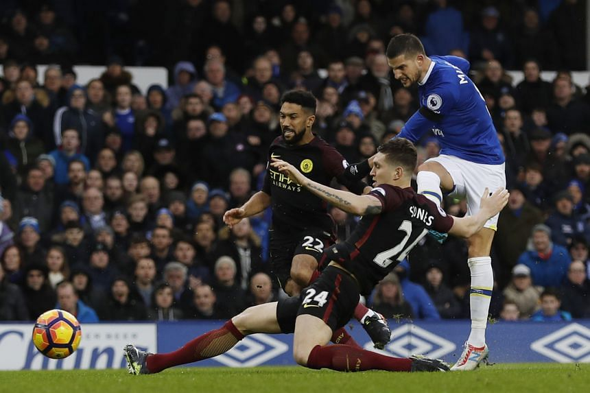 Everton midfielder Kevin Mirallas shooting past the despairing dive of Toffees old boy John Stones to score his side's second goal in the 47th minute as a hapless Gael Clichy looks on. Romelu Lukaku opened the scoring against Manchester City in the 3