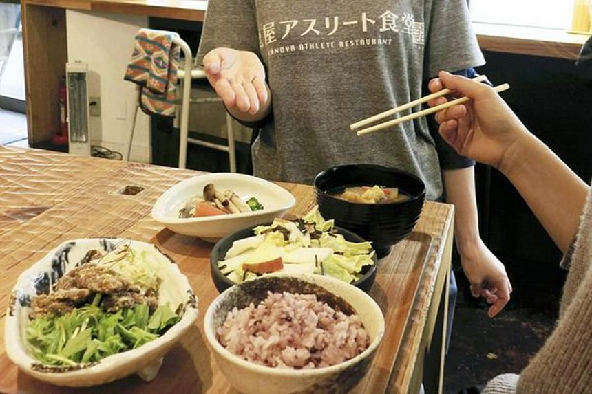 A dietitian at Kanoya Athlete Restaurant in Chiyoda Ward, Tokyo, showing some of the nutritionally balanced meals available. The food, based on the science of sports nutrition, is good for one's physical and mental health.