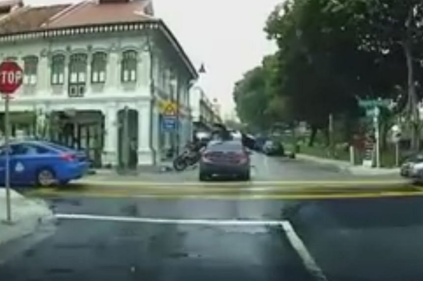 """A motorcycle delivery rider collided with a car, flew over it and landed on the road, at the junction of Tembeling Road and Koon Seng Road on Sunday. He is unhurt, said his employer. A resident in the area said the junction was a """"problematic"""" spot f"""
