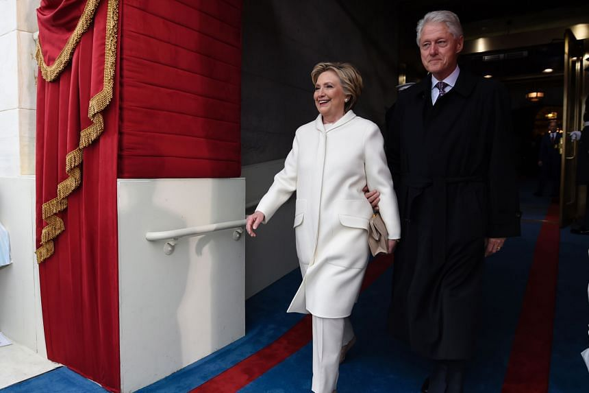 Mrs Clinton and her husband Bill arriving for the inauguration. She wore white too when she agreed to run on the Democrats' ticket. Mrs Trump has received praise for her choices - a Ralph Lauren dress, with Mr Trump (left), and a Herve Pierre number