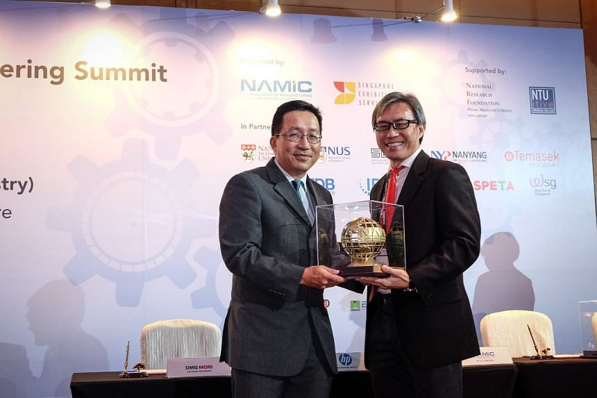 Mr Loh (left) receiving a token of appreciation, a 3D-printed metal globe emblazoned with Namic's logo, from Namic director Ho Chaw Sing at the opening of a summit on additive manufacturing yesterday.