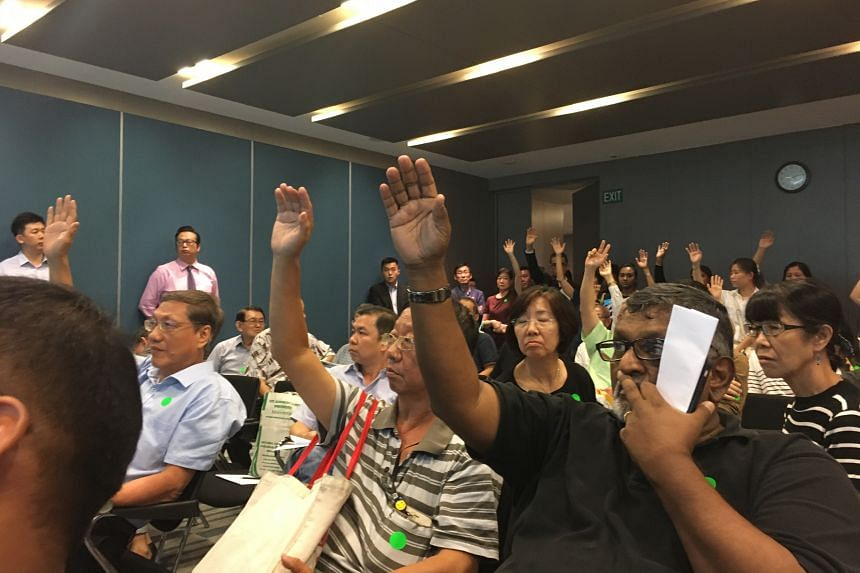 Shareholders and proxy holders of International Healthway Corp voting by a show of hands to adjourn the meeting, held at Maxwell Chambers, yesterday. The adjournment was voted down narrowly, 63 to 58.