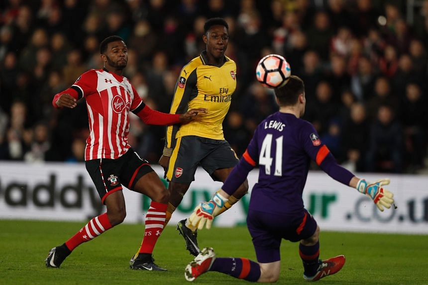 Danny Welbeck (centre) chips the ball over Southampton goalkeeper Harry Lewis to score Arsenal's opener. Welbeck scored a brace as the Gunners won 5-0 away in the fourth round of the FA Cup and now turn their attention to the Premier League, with a c