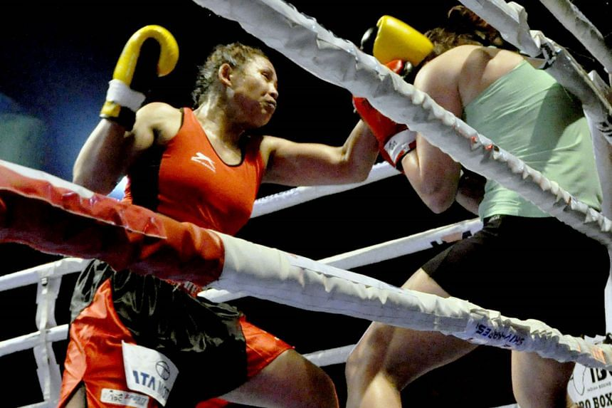 Laishram Sarita Devi pins Zsofia Bedo against the ropes on Sunday. Devi, who was making her professional debut, won the contest by a unanimous decision at the Khuman Lampak Stadium in Imphal, India.