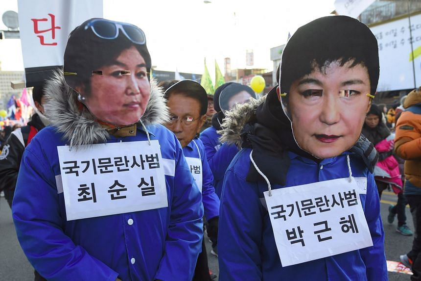Protesters in masks of Ms Park (right) and her friend at a rally in December.