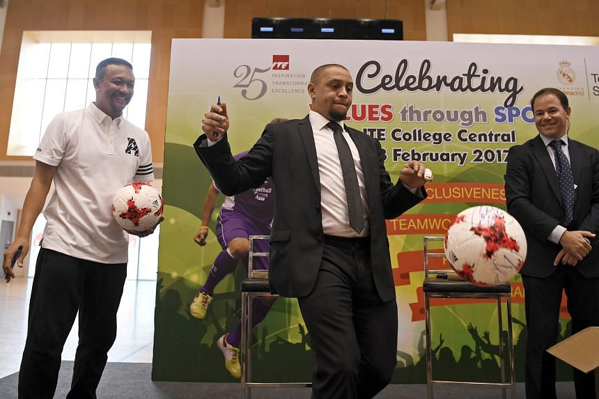 Roberto Carlos (centre) and Fandi Ahmad kicking signed footballs into the audience. The two were warmly feted by the 500 people at the ITE College Central.