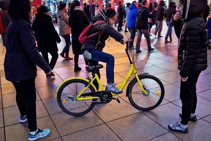 A girl riding an Ofo bicycle in Shanghai. After meeting with Shanghai officials, operators of Mobike, Ofo and Bluegogo promised to revamp equipment and security procedures to block underage users from accessing their bikes.