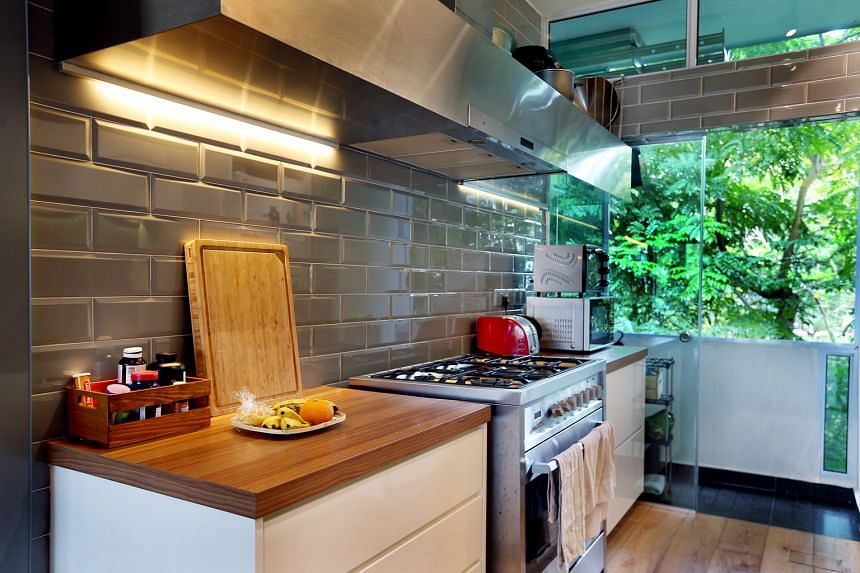 The wall separating the kitchen and living room was hacked and sliding glass doors were installed in its place, which helps open up the apartment. In the kitchen, dark tiles with plain-looking white cabinets made way for grey subway tiles and wooden