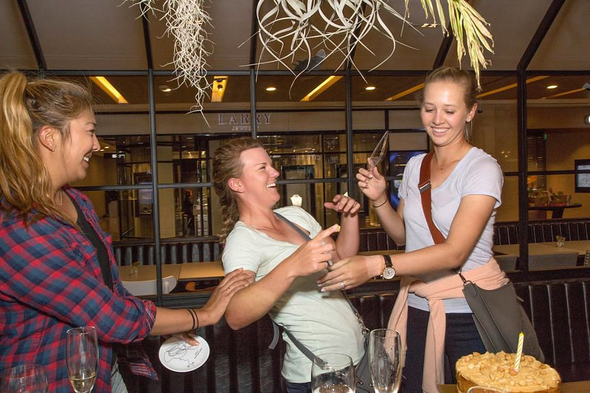 American golfers (from left) Alison Lee, Austin Ernst and Jessica Korda enjoying a surprise double birthday celebration for Lee (who turned 21 on Sunday) and Korda (23 yesterday) at the Greyhound Cafe in Paragon shopping centre yesterday. The trio, t